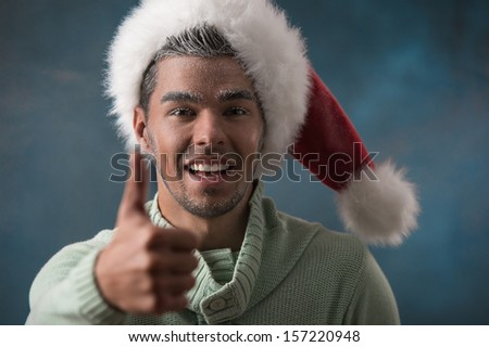 Curious man showing thumbs up in frost makeup wearing santa hat