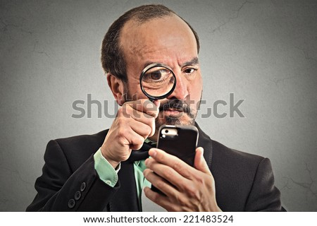Curious. Mature business man looking through a magnifying glass on smart phone isolated grey wall background. Human face expression. Investigator looking with magnifying glass. Security safety concept - stock photo