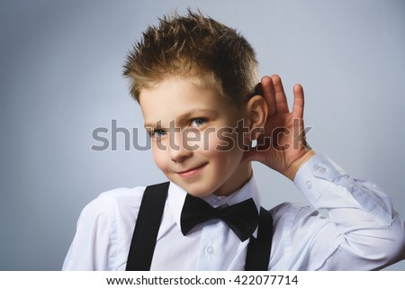 Curious smiling boy listens. Closeup portrait child hearing something, parents talk, hand to ear gesture isolated grey background. Human face expression, emotion, body language, life perception - stock photo