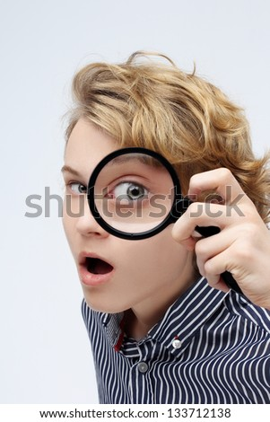 Curious teenage boy looking through magnifying glass at the camera. - stock photo