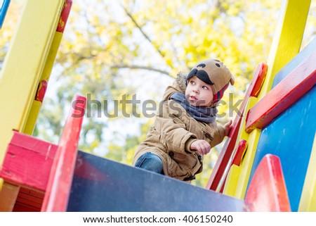 Curious Toddler boy climbing on  playground outdoors - stock photo