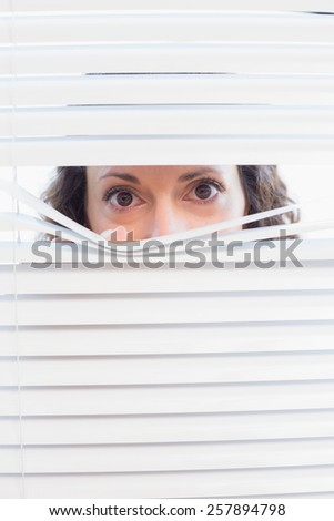 Curious woman looking through blinds in the house