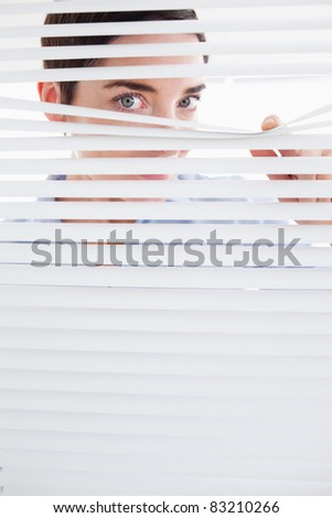 Curious Woman peeking out of a window in an office