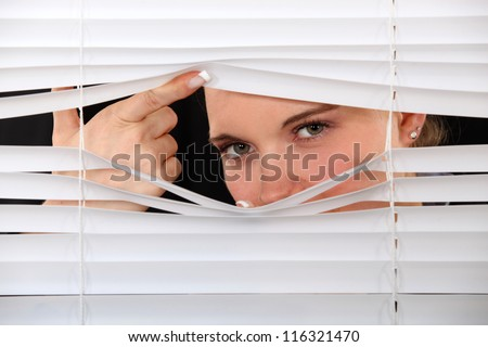 Curious woman peering through window blinds