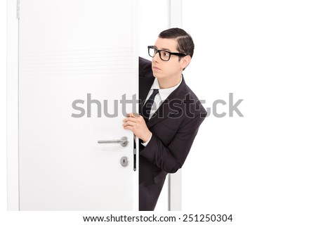 Curious young businessman looking through a door isolated on white background - stock photo