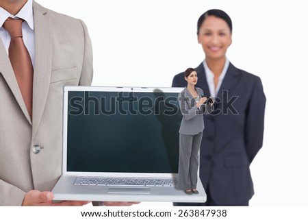 Curious young businesswoman with binoculars against laptop being presented by salesman with colleague behind him - stock photo