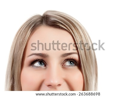 Curious young woman looking up - stock photo