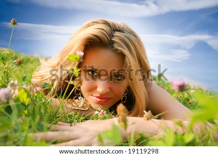Curious young woman lying on the grass - stock photo