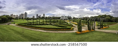 CURITIBA, BRAZIL - APRIL 10, 2014: Panoramic view of Curitiba in Parana, Brazil showcasing the architecture of the Curitiba Botanic Garden on a sunny day with locals passing by on April 10, 2015. - stock photo