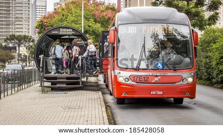 CURITIBA - MARCH 30: Curitiba's public transportation system, photographed on March 30, 2014 with a bus unloading and loading passengers on an integrated bus stop, is a landmark of Parana in Brazil. - stock photo