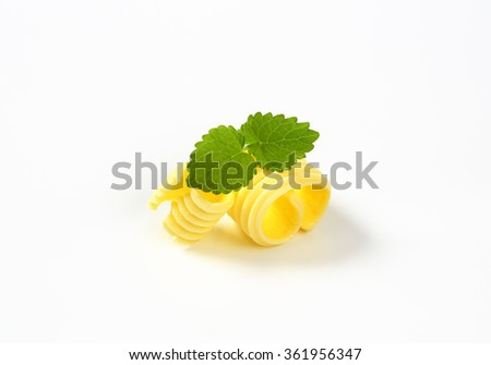 Curl of fresh butter on white background