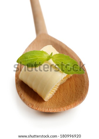 Curl of fresh butter with basil on wooden spoon, isolated on white