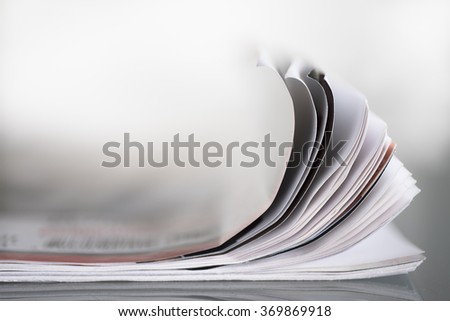 Curled papers of a closed magazine on a table with shallow depth of field - stock photo