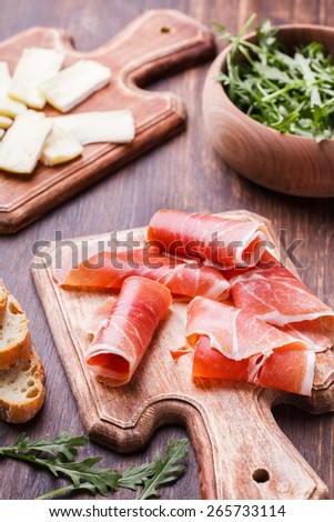 Curled Slices of  Prosciutto and the brie ,appetizer.selective focus - stock photo