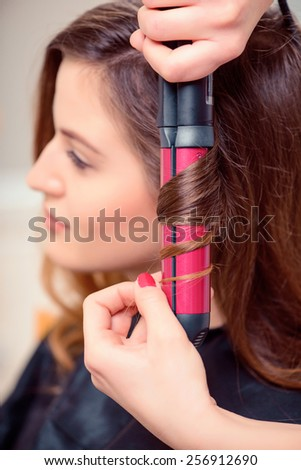Curled to perfection. Selective focus closeup of beautiful young woman getting her hair and makeup done in beauty salon  - stock photo