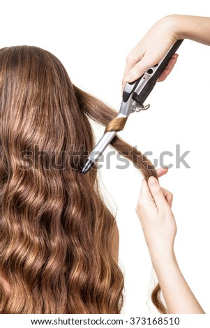 Curling iron and hair over isolated on white background