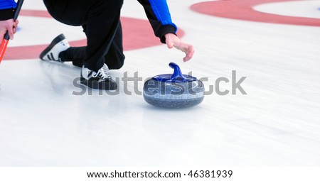 Curling player delivering a stone on a curling rink, sliding over the ice - stock photo