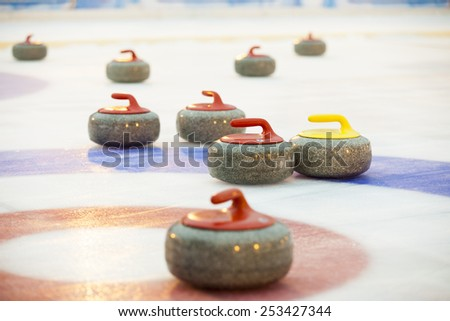 Curling stones on ice - stock photo