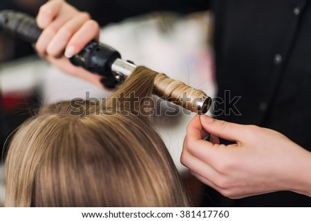 curling woman's hair giving a new hairstyle at hair salon close-up - stock photo