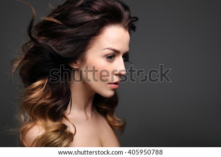 Curls, hair full of volume. Portrait of a beautiful woman on a black background.  - stock photo