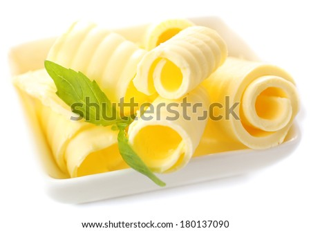 Curls of fresh butter with basil in bowl, isolated on white