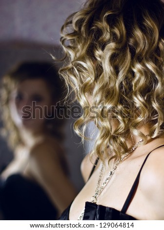 Curly air of woman looking in mirror - stock photo