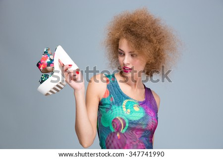 Curly attractive woman holding in her hand and stares at colorful summer shoe with white platform - stock photo