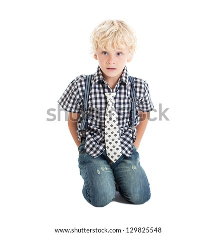 Curly blond boy sitting on the floor on his knees. The boy hiding his hands behind his back. Studio shot, isolated on white background. - stock photo