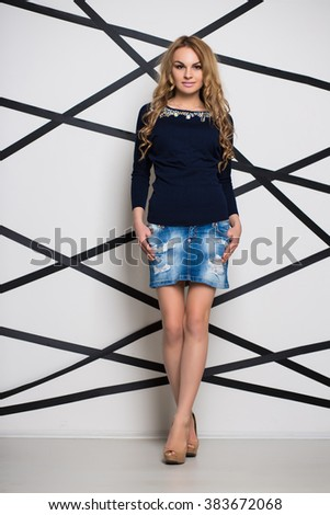 Curly blond woman posing in blue jeans skirt and blouse - stock photo