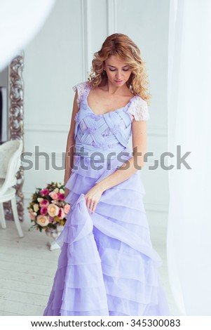 curly blonde in an elegant luxury purple dress in a light clean empty room