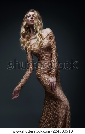 Curly blonde in gold dress (black background) - stock photo