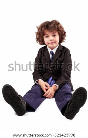 Curly boy in a jacket and tie sitting on the floor, smiling and looking at the camera. White background.