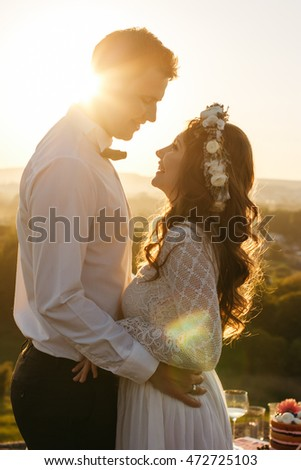 Curly bride in white wreathe smiles looking at a handsome groom in the rays of sunset