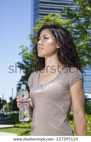 curly brunette woman with water plastic bottle at street - stock photo