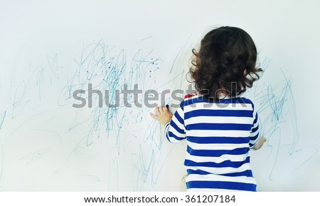 Curly cute little baby girl drawing with crayon color on the wall