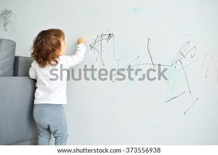 Curly Cute Little Baby Girl Drawing With Crayon Color On The Wall Works Of Child