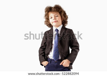Curly cute young boy stands in a business suit, smiling and looking into the camera, her head thrown back. Hands holding in their pockets. White background.