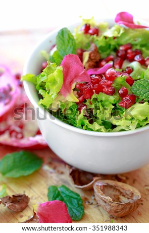 Curly endive salad with pomegranate, nuts, rose petals, peppermint, olive oil, balsamic vinegar and salt