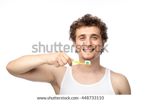 curly funny men with white undershirt brushing his teeth with care, isolated on white