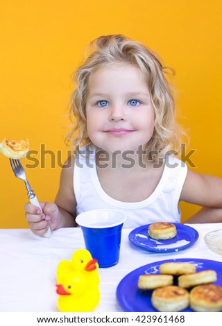 curly girl eating delicious cheesecakes morning cute little girl with a fork and cheese cakes on a yellow background
