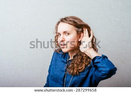 Curly girl  hear, hand near ear. Gray background. - stock photo
