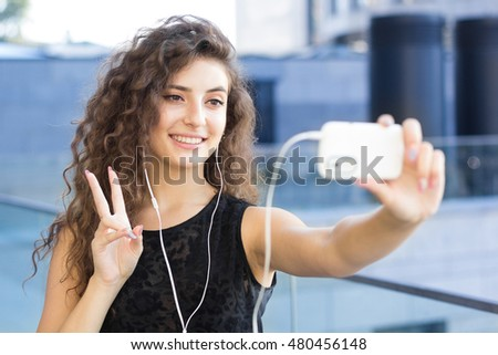 Curly girl holds a video chat with your friends, outdoors