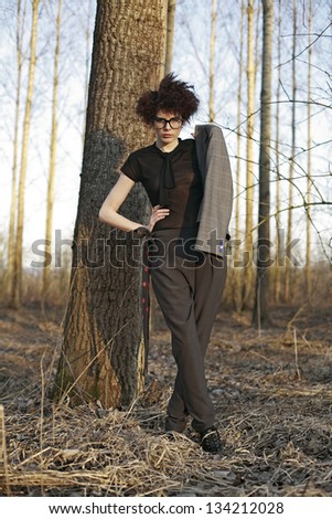 curly girl in autumn nature with glasses dressed like a man, hipster girl
