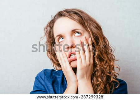 Curly girl is angry, his hands on his cheeks. Gray background. - stock photo