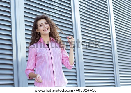 Curly girl laughing outdoors. Holds a lock of hair in the hands.