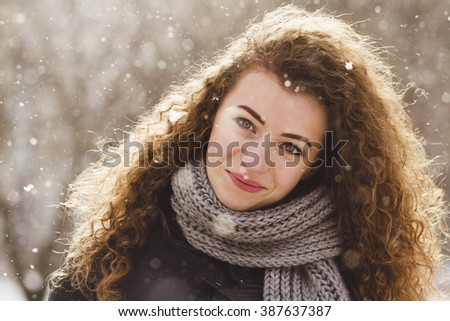 Curly girl on the background of snow