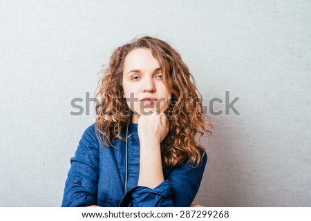 Curly girl sad thinking. The hand on  her head. Gray background. - stock photo