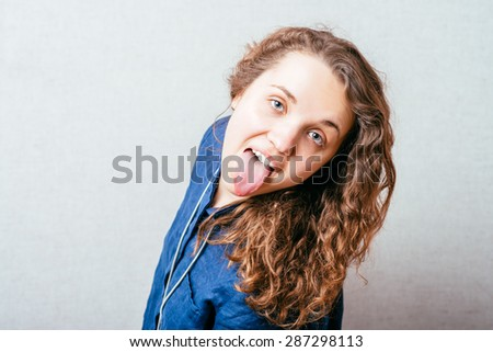 Curly girl shows tongue. Gray background.
