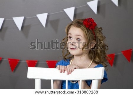 Curly girl sitting at the table with vase of red flowers. Isolated on grey background. - stock photo