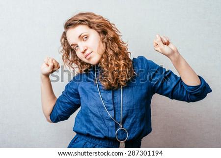 Curly girl stretches awake. Gray background. - stock photo